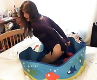 Kirsty puts sits in her paddling pool and pushes various chocolates inside her ass for a tasty treat.