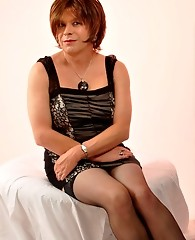 Horny crossdresser relaxing with a glass of wine